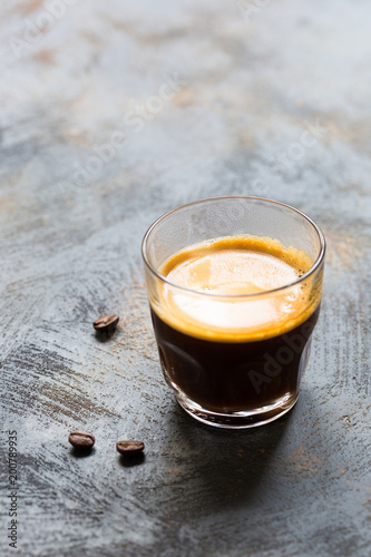Staande foto Thee Glass cup of fresh coffee time with thick golden foam froth on dark rustic background, espresso americano on black tissue with spoon of brown sugar and coffee beans, vertical copy space