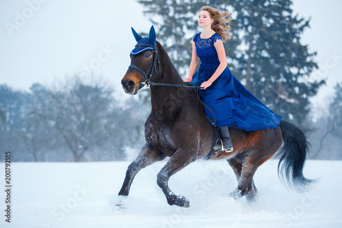 Photo Young girl in blue dress galloping horseback on winter field