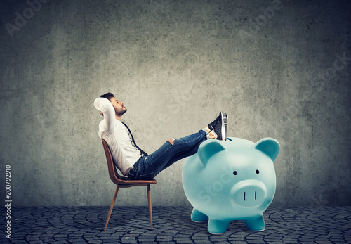 Fotografía  businessman with big piggy bank relaxing sitting on chair