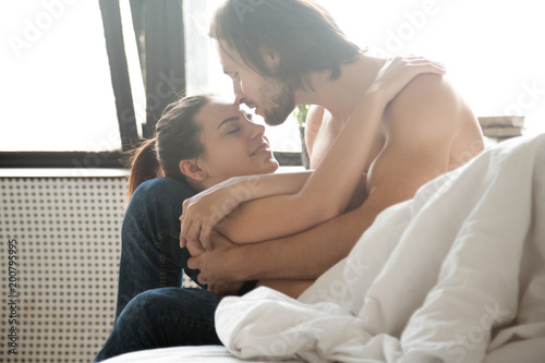 Young Couple In Love Embracing Relaxing On Bed Enjoying -6973