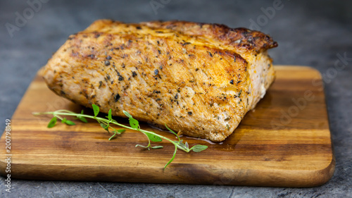 Fotografie, Obraz  Roasted pork tenderloin with thyme on the wooden cutting board