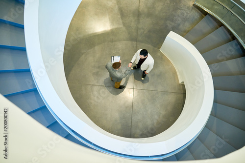 Papiers peints Spirale Directly above view of business partners shaking hands after successful completion of negotiations, spiral concrete staircase of modern office building on foreground