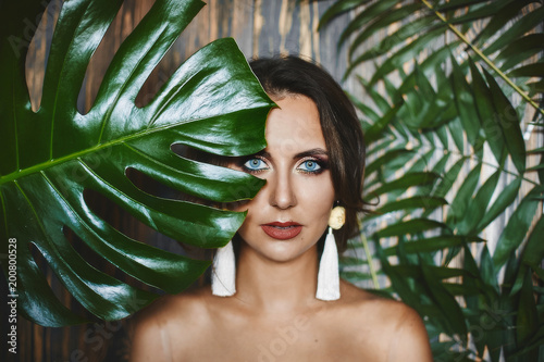 Fototapety, obrazy: Portrait of naked brunette model girl with amazing blue eyes and stylish earrings, looks through the big green leaves