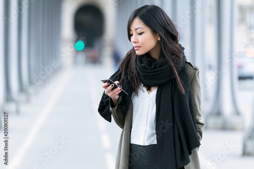 Stampa su Tela Concentrated asian young woman using her mobile phone in the street