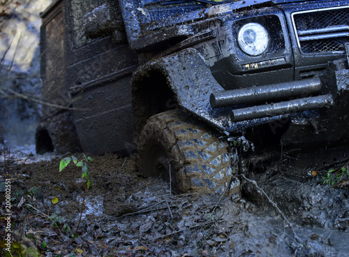 Fotografie, Obraz  Wheel in deep rut goes through mud and leaves trail.