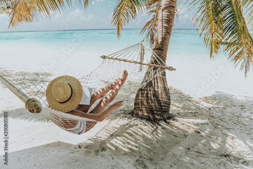 Photo Maldive islands. girl is relaxing in hammock and reading book