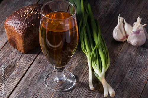 Staande foto Alcohol A glass of light beer, a loaf of black bread, fresh green onions and garlic lie on the table of old textured wooden boards