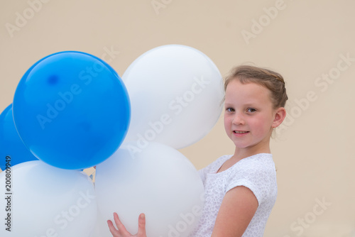 Little girl playing with balloons outdoor  Happy child wears