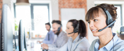 Obraz Call center worker accompanied by her team. - fototapety do salonu