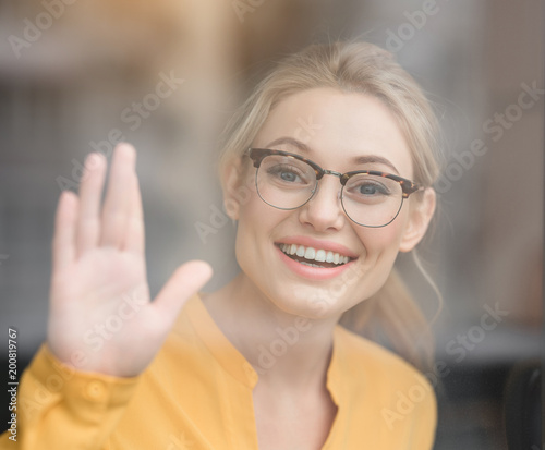 Hi portrait of cheerful young woman greeting someone inside glass portrait of cheerful young woman greeting someone inside glass and laughing m4hsunfo