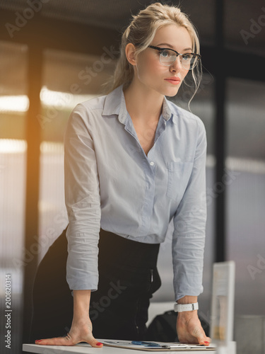 Portrait of serious businesswoman standing with documents and looking forward with confidence Canvas Print
