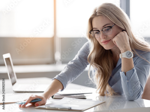 Portrait of successful young businesswoman reading document with concentration. She is sitting at desk in office