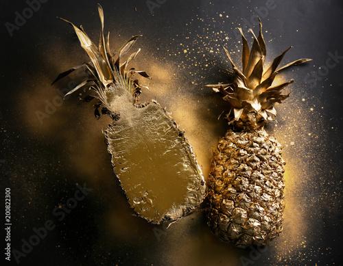 Golden pineapple halves on dark grey background, top view