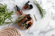 canvas print picture Bottles with rosemary essential oil on light background, top view