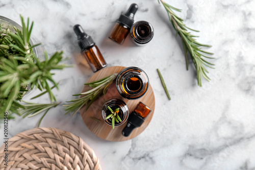 Bottles with rosemary essential oil on light background, top view