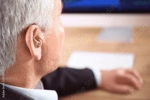 Mature man with hearing aid indoors Canvas Print
