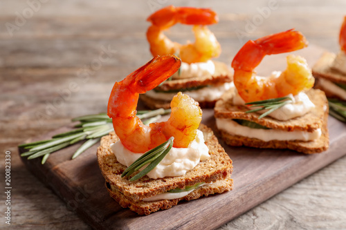 Delicious small sandwiches with shrimps on wooden board Wallpaper Mural