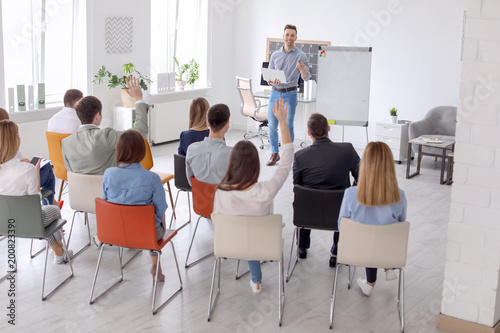 Fototapeta Male business trainer giving lecture in office