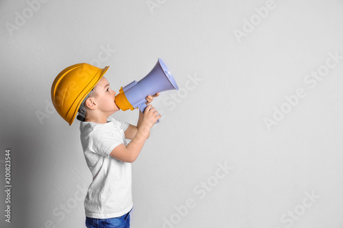 Fotografía  Adorable little boy in hardhat with megaphone on light background