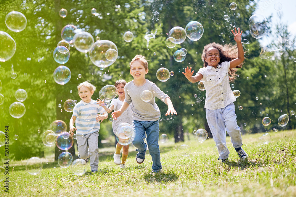 Fototapeta Multi-ethnic group of little friends with toothy smiles on their faces enjoying warm sunny day while participating in soap bubbles show