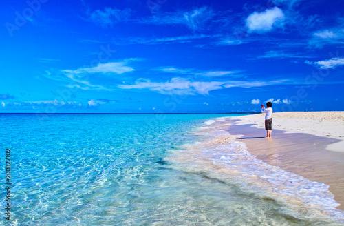 Staande foto Strand 真夏の宮古島。与那覇前浜ビーチの風景とスマホで写真撮影をする女性