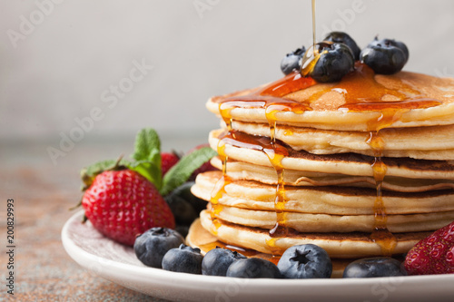 Fotografie, Obraz  Close-up delicious pancakes, with fresh blueberries, strawberries and maple syrup on a light background
