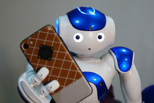 The Robot Holds The Phone In H...