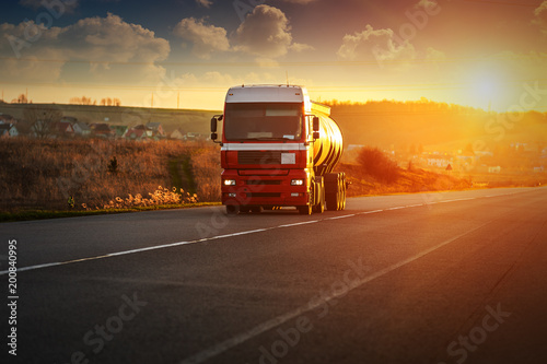 Foto op Plexiglas New York TAXI Arriving red truck on the road in a rural landscape at sunset