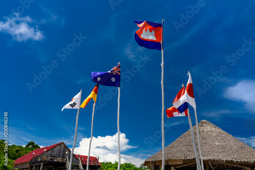 Flags hanged on the wooden beanpoles with many nationalities. Canvas Print
