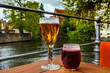canvas print picture - Two glasses of belgian beer standing on the table with Bruges city view