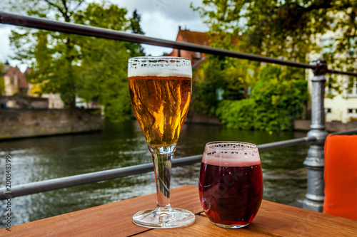 Tuinposter Brugge Two glasses of belgian beer standing on the table with Bruges city view