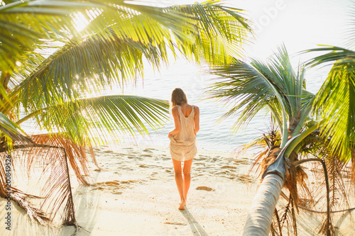 Papiers peints Statue rear view of woman standing between palm trees on sea beach
