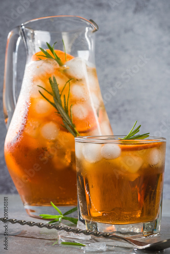 Fotografía  Ice cold tea in pitcher and glass with rosemary garnish