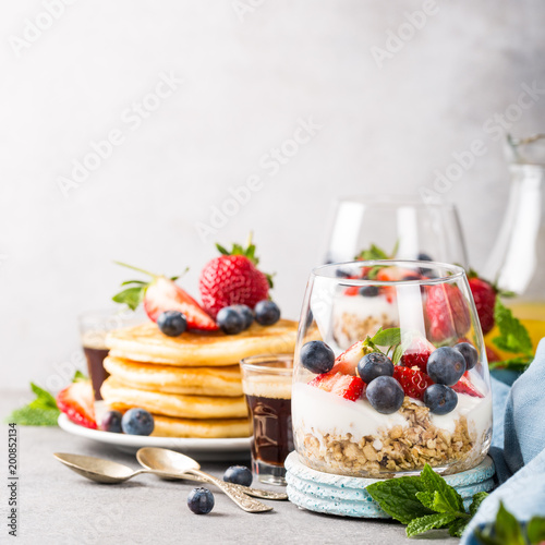 Papiers peints Jardin Oatmeal granola with berries and yogurt and panccakes on light gray concrete background. Healthy breakfast food concept with copy space.