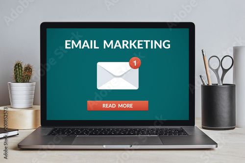 Email marketing concept on laptop screen on modern desk. All screen content is designed by me. Front view.