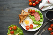 Fried egg, tomatoes, sausage, slices of bread and lettuce on a plate