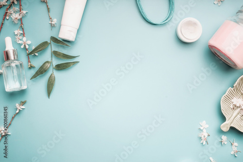 Fotografie, Tablou  Beauty concept with facial cosmetic products, green leaves and cherry blossom on pastel blue desktop background