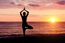 Woman At Sunset Practicing Yog...
