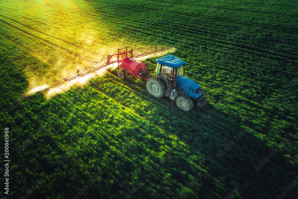 Fototapeta Aerial view of farming tractor plowing and spraying on field