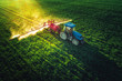 canvas print picture - Aerial view of farming tractor plowing and spraying on field