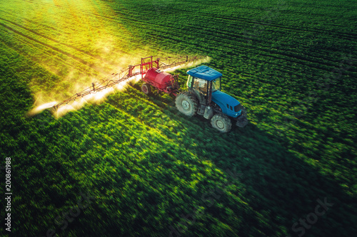 Fototapeta Aerial view of farming tractor plowing and spraying on field obraz