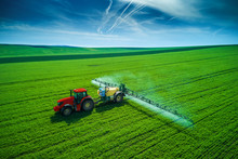 Aerial View Of Farming Tractor Plowing And Spraying On Field