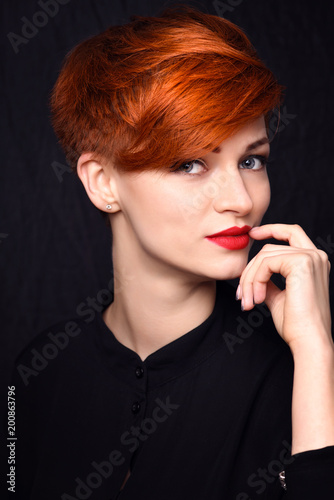 Fotografie, Obraz  Portrait of a beautiful young red-haired woman with short hair on a dark backgro