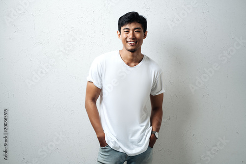 Foto  Smiling asian guy in white blank t-shirt, grunge wall, studio portrait