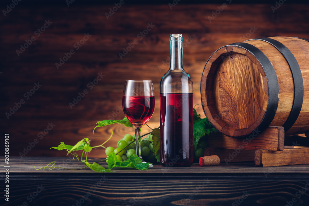 Wine bottle and glasses with wooden barrel on the table