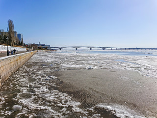 Road bridge over the Volga river between Saratov and Engels, Russia. Ice drift on the river in spring. Embankment in the city of Saratov. Sunny day in April.