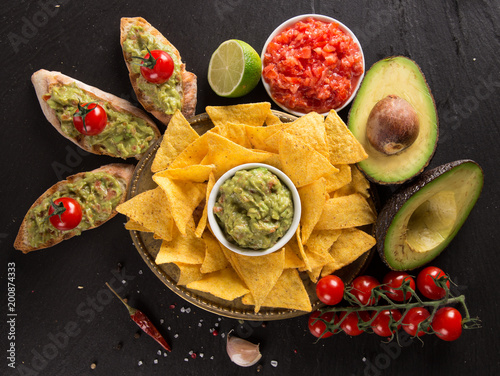 Staande foto Vlees Guacamole with bread and avocado on stone background