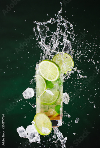 Fototapeta fresh mojito drink with liquid splash and crushed ice in freeze motion