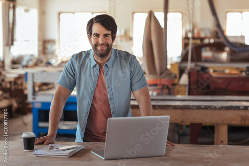 Smiling young woodworker using a laptop in his workshop