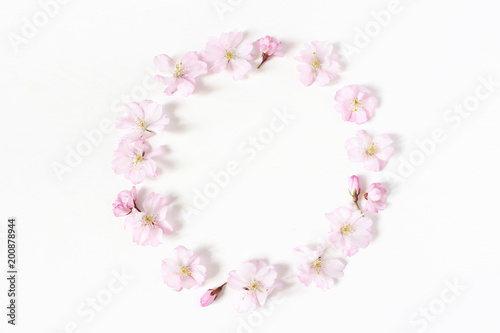 Styled stock photo. Spring, Easter feminine scene floral composition. Round frame wreath pattern made of pink Japanese cherry blossoms. White background. Flat lay, top view.